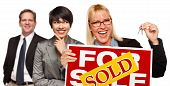 stock photo of real-estate-team  - Real Estate Team Behind with Blonde Woman in Front Holding Keys and Sold For Sale Real Estate Sign Isolated on a White Background - JPG