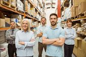 image of warehouse  - Smiling warehouse team with arms crossed in a large warehouse - JPG