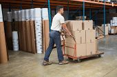 Worker pushing trolley with boxes in warehouse