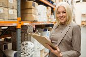 Smiling female manager holding clipboard in a large warehouse