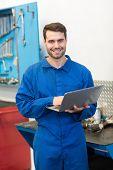 Mechanic smiling at the camera using laptop at the repair garage