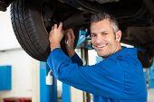 Smiling mechanic adjusting the tire at the repair garage