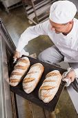 Baker taking tray of fresh bread out of oven in the kitchen of the bakery