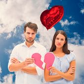 Upset couple holding two halves of broken heart against bright blue sky with clouds