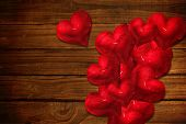Red love hearts against overhead of wooden planks