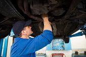 Mechanic examining under the car at the repair garage