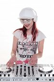 Young Fashionable Female Disc Jockey Mixing Music using DJ Mixer while Listening through Headphone. Isolated on White.