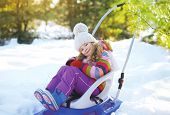 Happy Child Sitting In The Sled, Sunny Winter Day