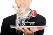 Businessman holding shopping cart on tablet.