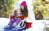 Winter And People Concept - Portrait Of A Mother And Child In The Sled Having Fun, Sunny Winter Day
