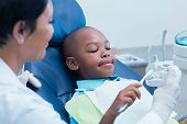 Female dentist teaching boy how to brush teeth in the dentists chair