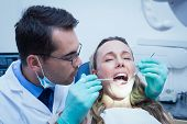 Dentist examining young womans teeth in the dentists chair