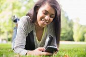 Pretty brunette using her smartphone in park on a sunny day