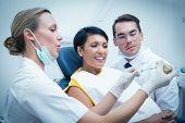 pic of false teeth  - Female dentist with assistant showing woman how to brush teeth in the dentists chair - JPG