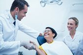 Male dentist shaking hands with woman in the dentists chair