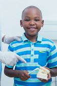 Cropped dentist teaching young boy how to brush teeth