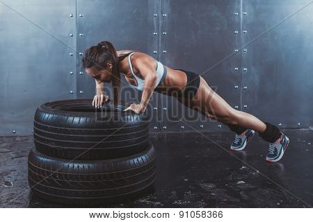 poster of Sportswoman. Fit sporty woman doing push ups on tire strength power training concept crossfit fitnes