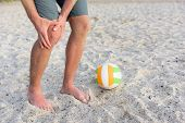 Постер, плакат: Injuries sports knee injury on man playing beach volleyball Male beach volley ball player with pa