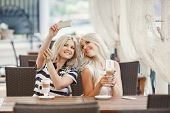 stock photo of internet-cafe  - Two young beautiful women - JPG