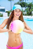 picture of pool ball  - Happy woman playing with ball in swimming pool on luxury beach resort - JPG
