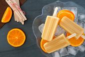 foto of popsicle  - Frozen orange yogurt popsicles in an ice filled bowl with fresh fruit slices against a slate background - JPG