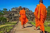 pic of buddhist  - Buddhist monks in traditional orange robes clothes walking in front of Angkor Wat temple - JPG