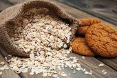 stock photo of oats  - Oatmeal cookies with oat flakes on a old wooden background  - JPG