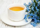 image of forget me not  - Cup of teand forget me not flowers on a wooden background - JPG