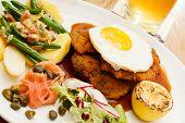 stock photo of wieners  - Wiener Schnitzel with Potatoes and Fresh Vegetables - JPG