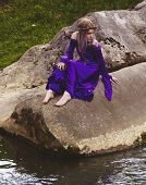 stock photo of fairyland  - Beautiful young woman wearing purple velvet gown and twig crown sitting on some rocks by a river - JPG