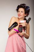 pic of hair curlers  - Young woman preparing for date having fun cute girl with curlers styling hair with many accessories comb brush hairdreyer on gray - JPG