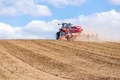 image of cultivator-harrow  - The tractor harrowing the large brown field in spring season - JPG