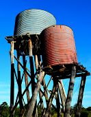 image of farm  - Typical scene on a Australian farm. This farm was deserted due to severe drought and all that remains are a few outbuildings, these tanks on leaning stands. ** Note: Visible grain at 100%, best at smaller sizes - JPG
