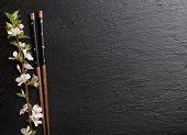 pic of sakura  - Japanese sushi chopsticks and sakura blossom on black stone background - JPG
