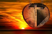 picture of cross-section  - Wooden Christian cross on a section of tree trunk hanging from a metal chain at the beautiful sunset over the sea with cloudy sky - JPG