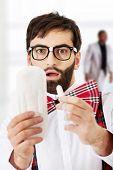 image of menstruation  - Surprised man wearing suspenders with menstruation pad - JPG