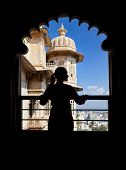 stock photo of rajasthani  - Woman silhouette on the balcony in City Palace museum of Udaipur Rajasthan India - JPG