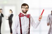 stock photo of suspenders  - Funny man wearing suspenders pointing up with big pencil - JPG