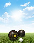 picture of jacking  - A set of wooden lawn bowls next to a jack on a perfect flat green lawn against a blue sky with white clouds - JPG