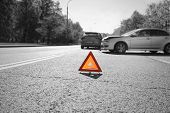 picture of hazardous  - Hazard warning triangle laid out on the road behind two crashed cars black and white photo with a red accent on a triangle - JPG