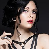 stock photo of gothic girl  - Beautiful Girl in the Gothic style with leather accessories and bright makeup - JPG