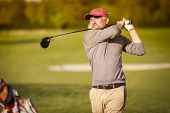 foto of swing  - Male golf player swinging driver golf club from tee box at dusk with beautiful atmosphere - JPG