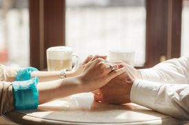 pic of women rights  - Young couple sitting in a cafe at a round white table - JPG