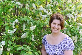 pic of denude  - An adult woman near blossoming bird cherry in the park - JPG