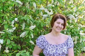 foto of denude  - An adult woman near blossoming bird cherry in the park - JPG