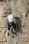 Blonde climber adjusting equipment
