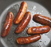 Pork sausages in frying pan.