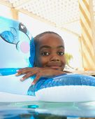 Young boy playing in an innertube in a swimming pool