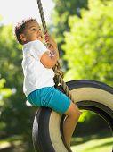 stock photo of tire swing  - Boy on tire swing - JPG