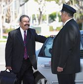Businessman and chauffeur at car